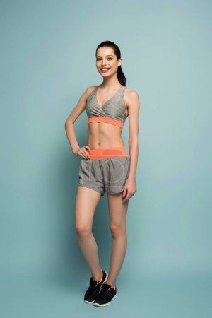 beautiful cheerful athletic girl standing in sportswear on blue