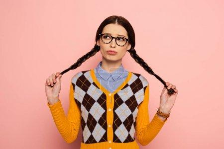 Photo pour Nerd femelle réfléchie dans les lunettes tenant des tresses sur rose - image libre de droit