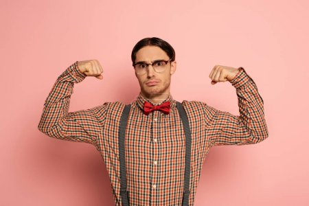 emotional male nerd in glasses showing muscles on pink