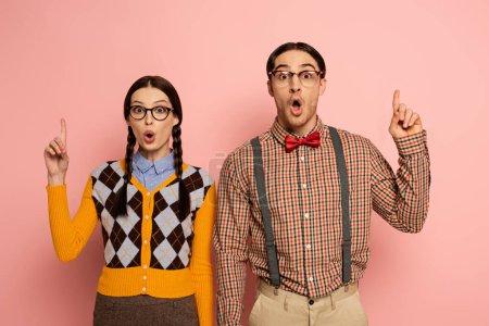 Photo pour Couple de nerds surpris dans les lunettes ayant l'idée et pointant vers le haut sur rose - image libre de droit