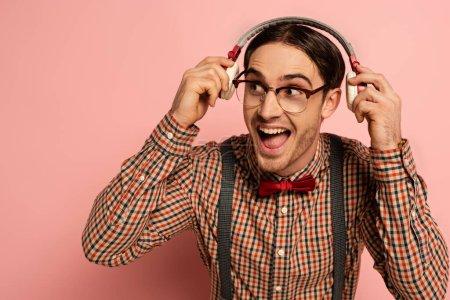 Photo pour Excité mâle nerd dans les lunettes écouter de la musique avec écouteurs sur rose - image libre de droit