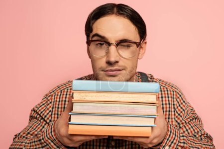 Photo pour Clin d'oeil mâle nerd dans des lunettes tenant des livres, isolé sur rose - image libre de droit