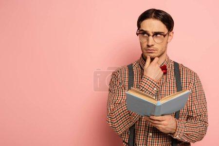 Photo pour Mâle réfléchi nerd dans les lunettes de lecture livre sur rose - image libre de droit
