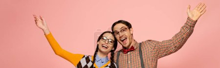 Photo for Panoramic shot of couple of happy nerds in eyeglasses gesturing and hugging, Isolated on pink - Royalty Free Image