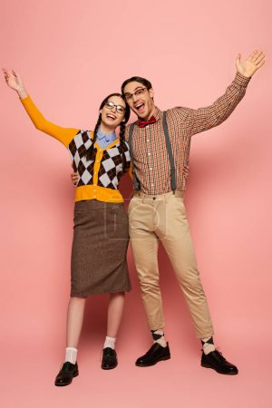 Photo for Couple of cheerful nerds in eyeglasses gesturing and hugging on pink - Royalty Free Image