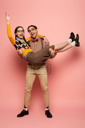 excited nerd in eyeglasses holding girlfriend on hands on pink
