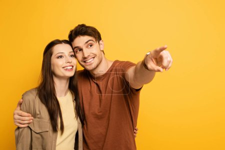Photo for Couple of happy beautiful travelers pointing isolated on yellow - Royalty Free Image