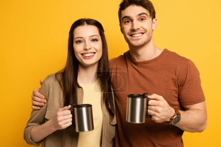 Photo for Couple of happy tourists holding cups with coffee, isolated on yellow - Royalty Free Image