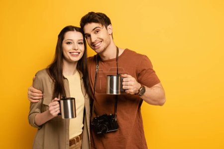 couple of smiling tourists with photo camera holding cups with coffee on yellow