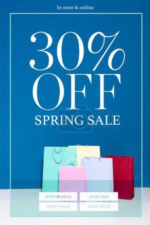Photo pour Sacs à provisions en papier coloré sur fond bleu, illustration de vente de printemps 30 pour cent off - image libre de droit