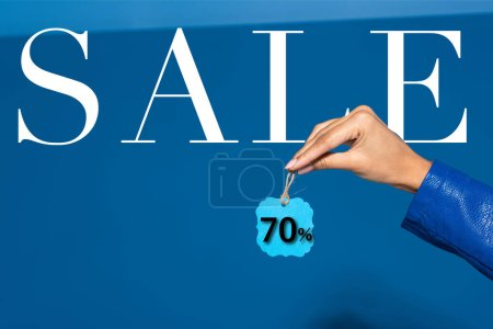 Photo pour Cropped view of african american woman holding label on blue background, 70 percent sale illustration - image libre de droit