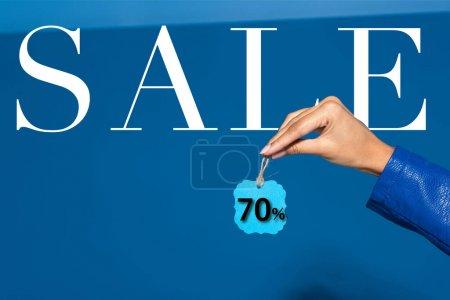Photo pour Vue recadrée de femme afro-américaine tenant étiquette sur fond bleu, 70 pour cent vente illustration - image libre de droit