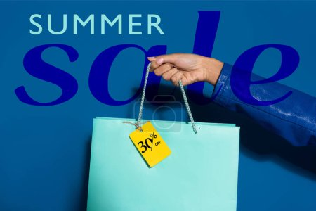 Photo pour Cropped view of african american woman holding shopping bag with label on blue, summer sale illustration - image libre de droit