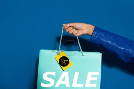Photo pour Cropped view of african american woman holding shopping bag with label on blue, 50 percent sale illustration - image libre de droit