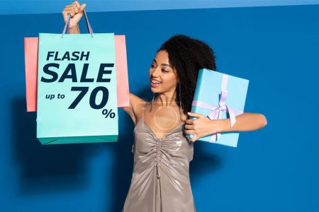 Foto de Happy beautiful african american woman in silver dress holding gift box and looking at shopping bags on blue background, flash sale illustration - Imagen libre de derechos