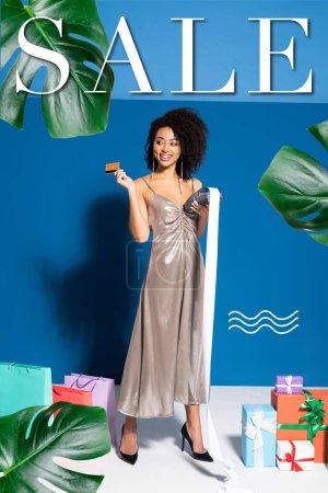 Photo pour Heureuse belle femme afro-américaine en robe d'argent tenant terminal de paiement avec chèque et carte de crédit près de cadeaux et sacs à provisions sur fond bleu, illustration de vente - image libre de droit