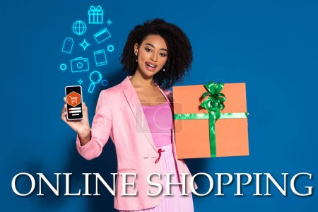 Photo pour Élégante femme afro-américaine souriante avec cadeau montrant smartphone avec illustration de shopping en ligne sur fond bleu - image libre de droit