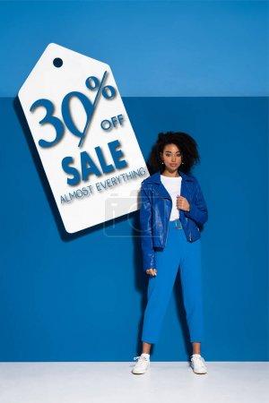Photo pour Afro-américaine près de grand prix blanc étiquette sur fond bleu, 30 pour cent hors vente illustration - image libre de droit