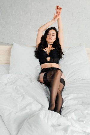 attractive passionate girl in black lingerie and stockings lying in bed
