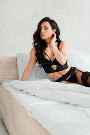 Photo pour Foyer sélectif de belle femme sexy en lingerie noire et bas assis sur le lit - image libre de droit