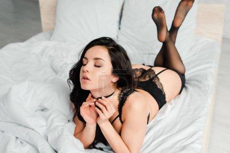 Photo pour Jolie brune en lingerie noire et bas couchés au lit - image libre de droit