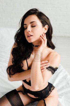 Photo pour Jolie fille sensuelle en lingerie noire assise sur le lit - image libre de droit