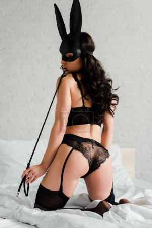Photo pour Back view of sensual female dominant in erotic rabbit mask holding spanking paddle on bed - image libre de droit