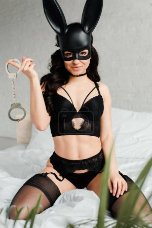 beautiful smiling sexy woman in erotic rabbit mask holding handcuffs on bed