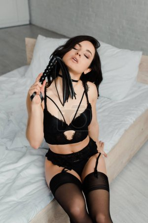 Photo for Sensual female dominant in erotic lingerie holding flogging whip while sitting on bed - Royalty Free Image