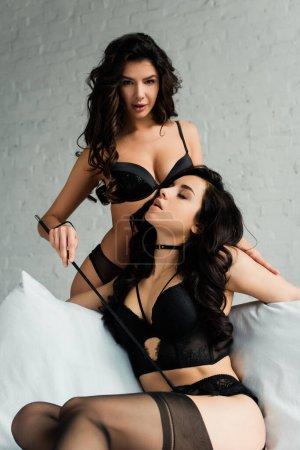 Photo pour Couple homosexuel sexy en lingerie noire jouant avec une pagaie fessée dans la chambre à coucher - image libre de droit