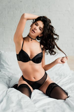 Photo for Attractive sensual girl in black lingerie and stockings sitting on bed - Royalty Free Image