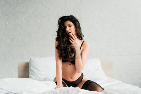 Photo for Beautiful seductive girl in black lingerie and stockings sitting on bed - Royalty Free Image