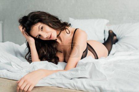 Photo pour Fille passionnée souriante en lingerie noire et bas dans la chambre - image libre de droit