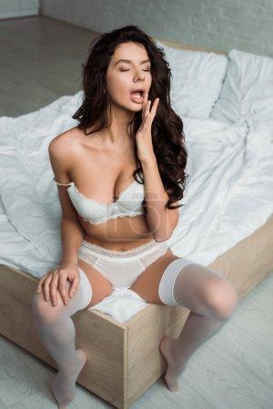 Photo pour Passionnée jeune femme en lingerie blanche et bas assis sur le lit - image libre de droit