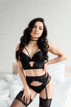 Photo pour Jolie femme sexy en lingerie noire et bas dans la chambre - image libre de droit