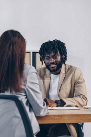 Photo pour Orientation sélective d'un recruteur africain-américain menant un entretien d'embauche avec un employé en poste - image libre de droit