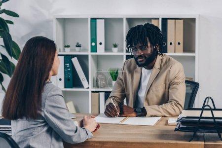 Photo pour Recruteur afro-américain avec stylo et cahier menant un entretien d'embauche avec un employé en poste - image libre de droit