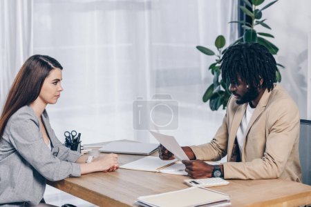 African american recruiter looking at papers in front of employee at table in office