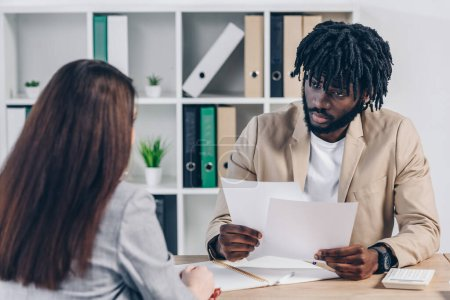 Selective focus of african american recruiter holding papers and looking at employee at table in office