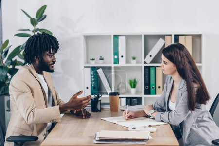 Photo pour Recruteur et employé américain d'origine africaine discutant lors d'un entretien d'embauche au bureau - image libre de droit