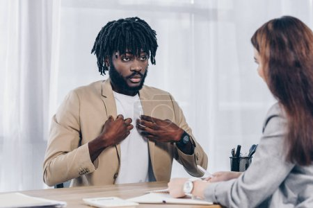 Selective focus of african american employee pointing oneself and looking at recruiter at job interview in office