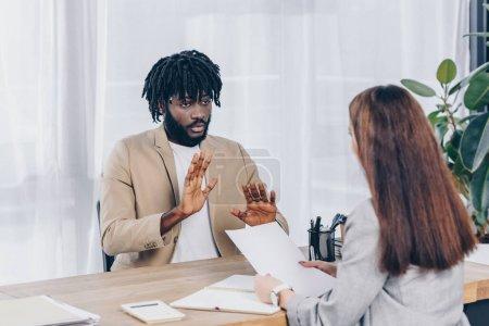 Photo pour Concentration sélective du recruteur avec du papier et un employé afro-américain parlant lors d'un entretien d'embauche au bureau - image libre de droit