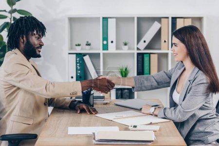 Photo pour Un recruteur et un employé afro-américain se serrent la main, se regardent et sourient au bureau - image libre de droit
