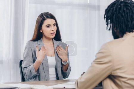 Photo pour Orientation sélective d'un employé qui se montre du doigt et qui parle à un recruteur américain d'origine africaine lors d'un entretien d'embauche au bureau - image libre de droit