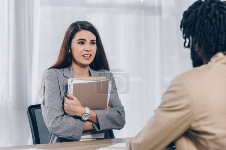 Photo for Selective focus of worried employee with documents and african american recruiter looking at each other at job interview in office - Royalty Free Image