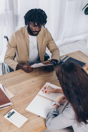 Photo pour Vue en grand angle du recruteur handicapé afro-américain tenant des papiers et regardant l'écriture des employés dans un carnet - image libre de droit