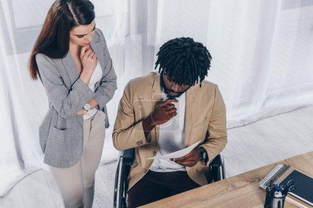 Photo pour Vue en angle élevé d'un employé réfléchi près d'un recruteur handicapé afro-américain avec des papiers au bureau - image libre de droit