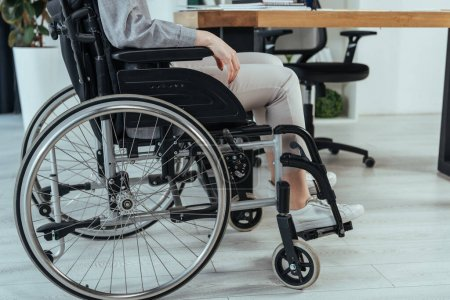 Photo pour Partial view of disabled employee in wheelchair at table in office - image libre de droit
