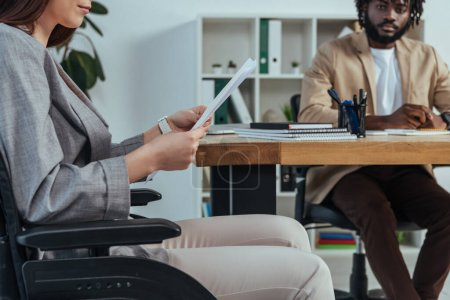 Disabled employee in wheelchair with papers and african american recruiter at table in office