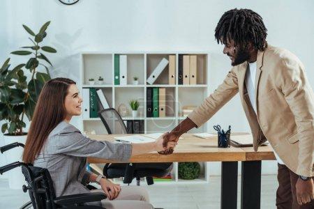 Photo pour Un employé handicapé et un recruteur américain d'origine africaine se serrent la main lors d'un entretien d'embauche - image libre de droit